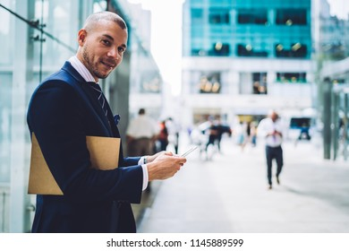 Portrait of cheerful young entrepreneur with folder holding smartphone and updating profile in app using 4G internet.Positive successful businessman in formal wear chatting online on cellular