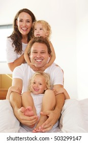 Portrait of cheerful young family of four in bed at home