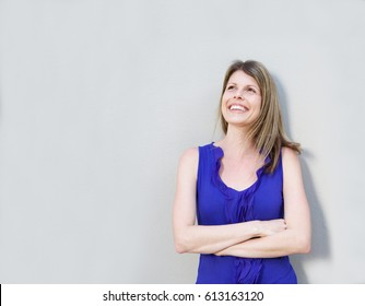 Portrait of cheerful young female model standing with arms crossed and looking away against gray background