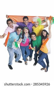 Portrait of cheerful young friends cheering with Indian flag over white background