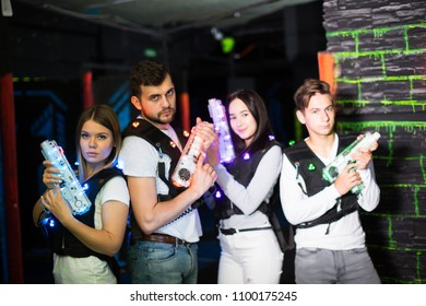 Portrait of cheerful young friends with laser guns during lasertag game in dark room