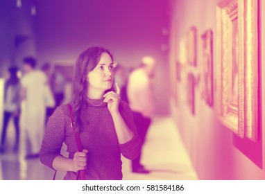 Portrait of cheerful young girl attentively looking at paintings in art museum