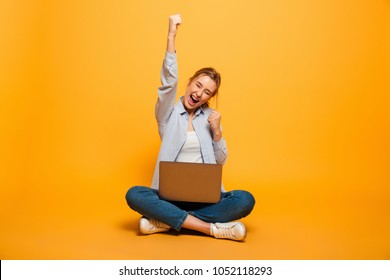 Portrait of a cheerful young girl with braces sitting on a floor with a laptop computer and celebrating success isolated over yellow background