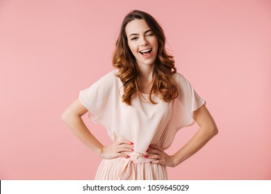 Portrait of a cheerful young girl in dress looking at camera and winking isolated over pink background