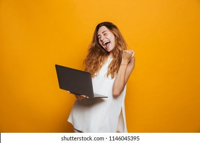 Portrait of a cheerful young girl holding laptop computer and celebrating success isolated over yellow background