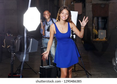 Portrait of cheerful young girl on background with professional photographer during photo shoot on town street