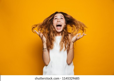 Portrait of a cheerful young girl screaming isolated over yellow background