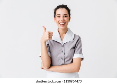 Portrait of a cheerful young housemaid dressed in uniform showing thumbs up gesture isolated over white background