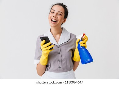 Portrait of a cheerful young housemaid dressed in uniform and rubber gloves using mobile phone while holding sprayer isolated over white background