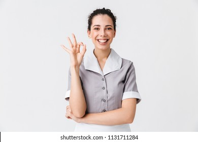 Portrait of a cheerful young housemaid dressed in uniform showing ok gesture isolated over white background