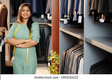 Portrait of cheerful young Indian shop assistant standing in store with arms folded and looking at camera