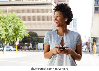 Portrait of cheerful young lady out on the city street listening to music on her mobile phone