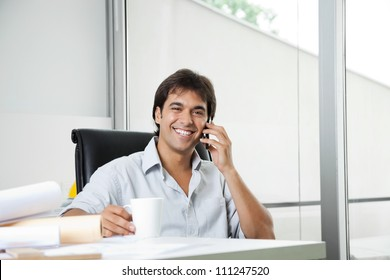 Portrait of cheerful young male architect answering phone call while having coffee