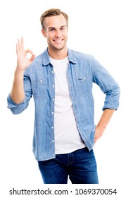 Portrait of cheerful young man in blue smart casual clothing, showing okay gesture, isolated over white background. Emotions and success concept.