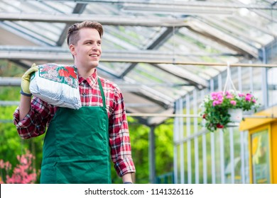 Portrait of a cheerful young man carrying a bag of high-quality potting soil while working as floristry specialist in a modern flower shop