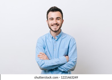 Portrait of cheerful young man in casual with crossed arms smiling over white background and looking at the camera