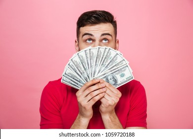 Portrait of a cheerful young man holding money banknotes and looking up at copy space isolated over pink background