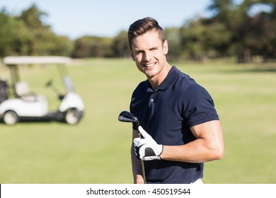 Portrait of cheerful young man holding golf club while standing on field