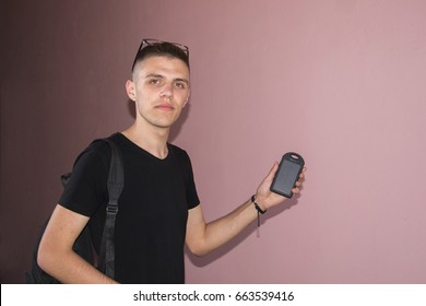 Portrait of cheerful young man holding powerbank