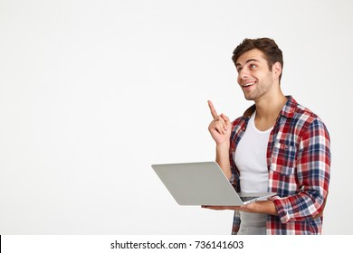 Portrait of a cheerful young man holding laptop computer while standing and pointing finger up isolated over white background