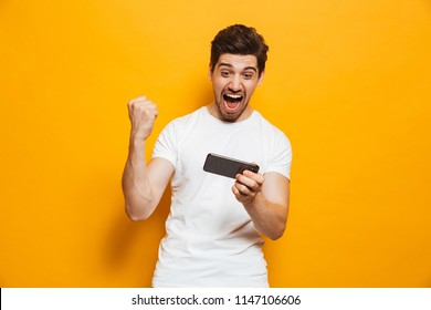 Portrait of a cheerful young man playing games on mobile phone isolated over yellow background