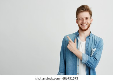 Portrait of cheerful young man smiling looking at camera pointing finger up over white background.