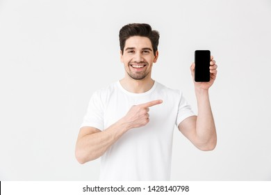 Portrait of a cheerful young man wearing casual clothing isolated over white background, showing blank screen mobile phone