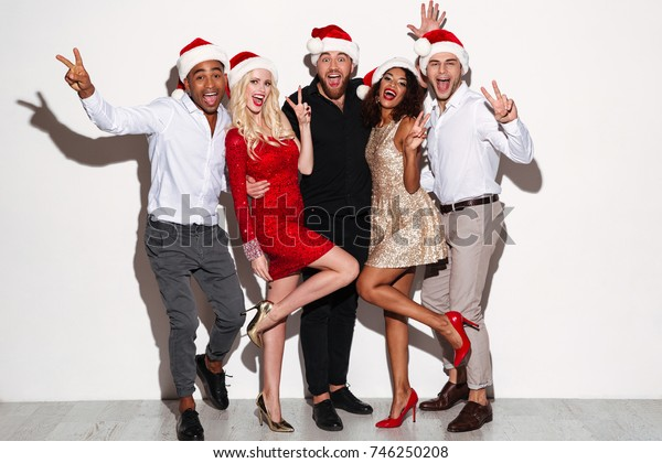 Portrait of a cheerful young multiracial group of friends celebrating New Year together while standing and showing peace gesture isolated over white background
