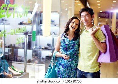 Portrait of cheerful young people with colorful shopping bags smiling at camera