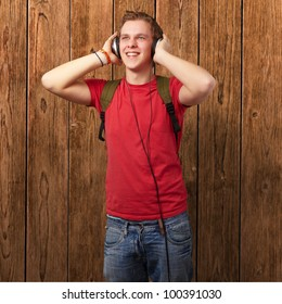 portrait of a cheerful young student listening to music with headphones over a wooden wall
