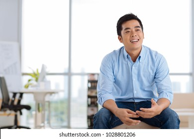 Portrait of cheerful young Vietnamese businessman