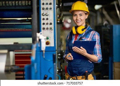 Portrait of cheerful young warehouse employee looking at camera with charming smile while doing checklist, she holding clipboard in hands