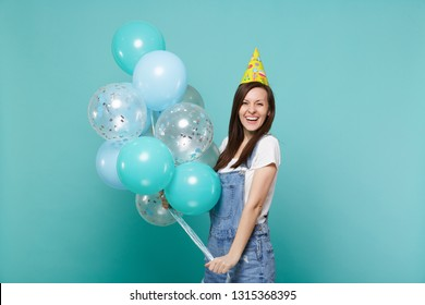 Portrait of cheerful young woman in denim clothes, birthday hat celebrating, holding colorful air balloons isolated on blue turquoise wall background. Birthday holiday party, people emotions concept
