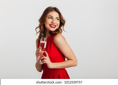 Portrait of a cheerful young woman dressed in red dress holding glass of champagne and looking away isolated over white background
