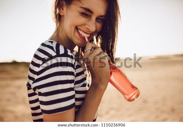 Portrait von fröhlicher junger Frau trinken Getränk mit Stroh aus Glasflasche. Mädchen trinken an einem Sommertag eine Limonade im Freien.