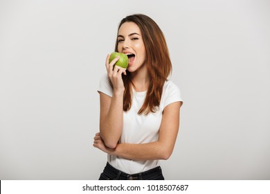 Portrait of a cheerful young woman eating green apple isolated over white background
