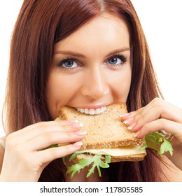 Portrait of cheerful young woman eating sandwich with cheese, isolated over white background