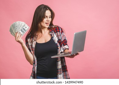 Portrait of a cheerful young woman holding money banknotes and celebrating isolated over pink background. Using laptop.