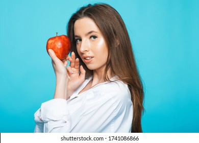 Portrait of a cheerful young woman holding red apple and looking away isolated over blue background