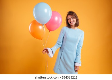 Portrait of cheerful young woman holding colorful balloons