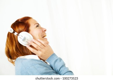 Portrait of a cheerful young woman laughing while having fun listening to music