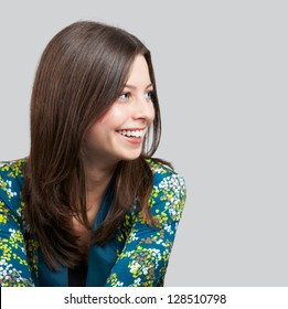 Portrait of a cheerful young woman over grey background.