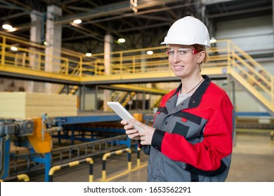 Portrait of cheerful young woman in protective goggles and hardhat checking data on tablet at construction plant