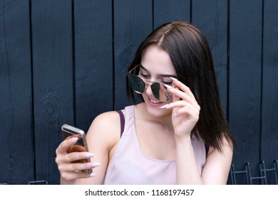 Portrait of cheerful young woman reading something on mobile phone and laughing. Adorable brunette model posing outside on wooden wall. Technology concept