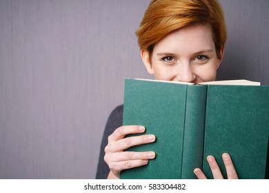 Portrait of cheerful young woman with red short hair peeping out of green book and smiling while standing over grey background