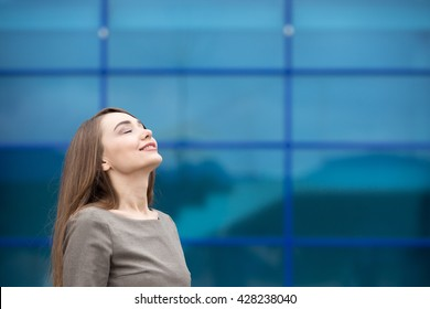 Portrait of cheerful young woman relaxing outdoors with closed eyes. Happy beautiful caucasian woman breathing fresh air on the street in summer. Copy space