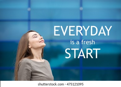 """Portrait of cheerful young woman relaxing outdoors with closed eyes. Happy beautiful successful female breathing fresh air on the street in summer. Motivational text """"Everyday is a fresh start"""""""