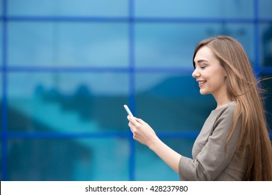 Portrait of cheerful young woman sending message on smartphone outdoors. Happy beautiful caucasian woman using mobile phone, making call, looking at screen on the street in summer. Copy space