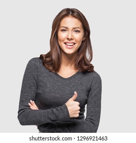 Portrait of cheerful young woman showing thumb up sign, over gray background