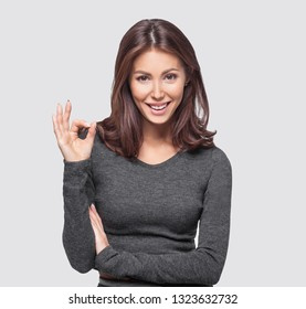 Portrait of cheerful young woman showing okay sign. Isolated over gray background. Studio shot